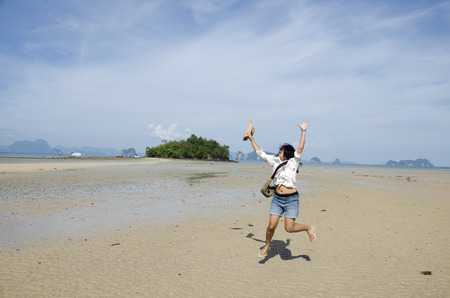 yai: Thai woman jumping and portrait for take photo on the beach way or tombolo sea go to small island in the andaman ocean while sea water level decreased at Koh Yao Noi in Phang Nga, Thailand Stock Photo