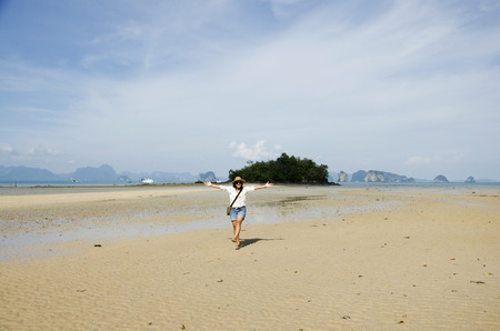 decreased: Thai woman walking and portrait for take photo on the beach way or tombolo sea go to small island in the andaman ocean while sea water level decreased at Koh Yao Noi in Phang Nga, Thailand