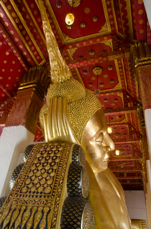Big golden reclining buddha statue in ubosot or chapel at Wat Pa Mok Worawihan temple Stock Photo