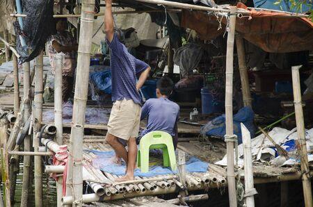 Fisher man thai mensen bereiden gereedschappen voor het vissen in de nacht op vissersdorp in houten huis op Pak Nam Prasae stad op 10 augustus 2016 in Rayong, Thailand Redactioneel