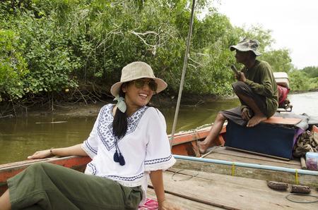 De Thaise oude mensenvervoer lange staartboot brengt mensenreisbezoek en kijkt rivieroever en Mangrovenbos van de stad van Pak Nam Prasae op 10 Augustus, 2016 in Rayong, Thailand