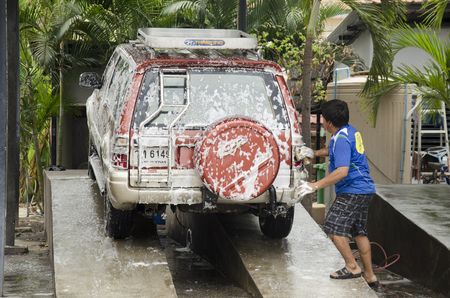 dirty car: Thai people workers cleaning and washing car at local carwash station on August 12, 2016 in Nonthaburi, Thailand Editorial