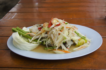 Thai cuisine Som Tum or thai food fruit spicy green papaya salad with blue crab in plate