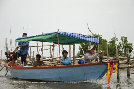 Thaise oude man met lange staartboot brengt mensen naar huis na het vissen in het overzees bij de stad van Pak Nam Prasae op 10 Augustus, 2016 in Rayong, Thailand