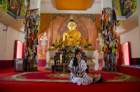 phon: Asian thai woman visit and praying buddha statue in ubosot at Wat Phon Chai and travel Phi Ta Khon Museum on February 22, 2017 in Loei, Thailand.