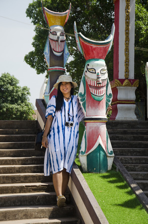 phon: Asian thai woman travelers visit and portrait with Phi Ta Khon statue for writing blog at Phi Ta Khon Museum in Wat Phon Chai on February 22, 2017 in Loei, Thailand.