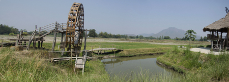 Thai Dam Cultural Village and big wooden turbine baler water wheel or wood noria water with landscape rice field mountain in Chiang Khan at Loei, Thailand