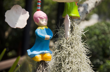 Clay girl doll hanging on the tree for decoration in garden at outdoor of home