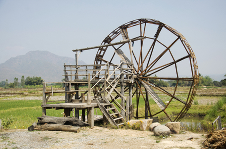 Big wooden turbine baler water wheel or wood noria water with landscape rice field mountain at Thai Dam Cultural Village in Chiang Khan at Loei, Thailand