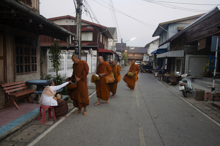 Thai people put food offerings to monks procession walk on the road of tradition of almsgiving with sticky rice at Chiang Khan on February 22, 2017 in Loei, Thailand. Editorial