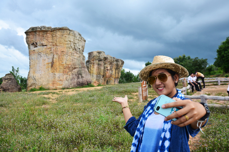 Thai women people travel and posing shooting photo with Mor Hin Khao or Thai Stonehenge in the Phu Laenkha National Park considered as a beautiful viewpoint located in Chaiyaphum , Thailand