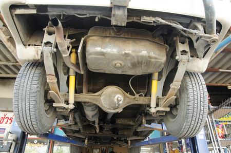 auto hoist: Thai mechanic professional motor repair and maintenance change oil and Check availability of car at local garage shop on December 19, 2016 in Nonthaburi, Thailand