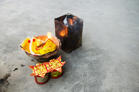 People burn joss paper gold and silver paper for worship with paper made to resemble money and burned as sacrificial offering for pray to god and memorial to ancestor in Chinese new year day at house Stock Photo