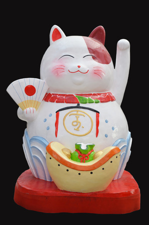 Japanese maneki neko lucky welcoming cat on black background Stock Photo