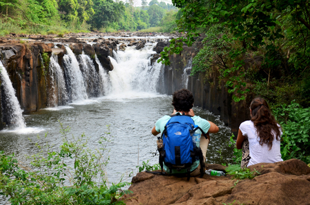 Foreigners travelers lovers sitting and relax on stone at viewpoint of Tad Pha Suam waterfalls on May 2, 2015 in Pakse, Champasak, Laos. Editorial