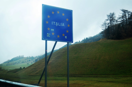 Sign display of border of Italy at beside road