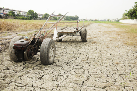Damage old Tractor and Trailer towing stop on Paddy field wait spring season on desert land because drought disaster in countryside of Thailand Stock Photo