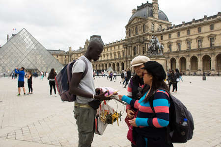 the grand daughter: Asain women mother and daughter buying souvenir gift from African-French Louvre Pyramid at Musee du Louvre or the Grand Louvre Museum on September 5, 2017 in Paris, France