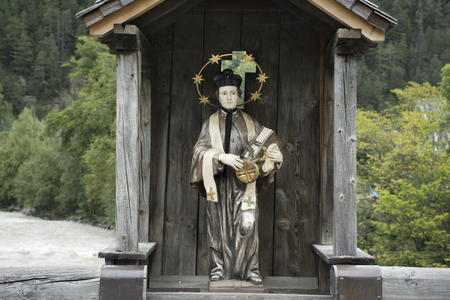 St. Lukas statue in wooden cottage on old bridge over Bad inn river at Pfunds village in evening time in Tyrol, Austria Editorial