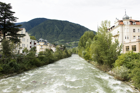View cityscape and landscape with Italian people and foreigner travelers walking on the bridge crossover passer river at Meran city on September 2, 2017 in Merano, Italy Editorial
