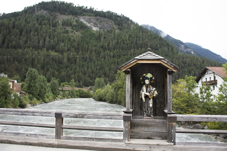St. Lukas statue in wooden cottage  on old bridge over Bad inn river at Pfunds village in evening time in Tyrol, Austria