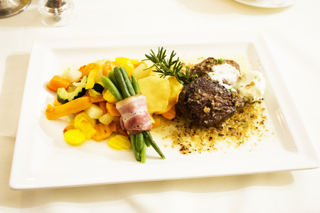 Steak beef and gravy sauce with fried vegetable mix and ham roll up long bean on ceramic plate serve dinner in restaurant at Pfunds village in Tyrol, Austria Stock Photo