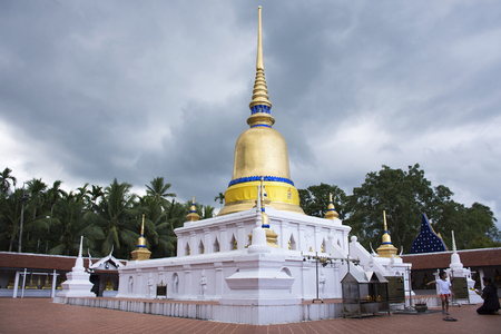 Thai people and foreigner travelers visit with praying golden chedi and buddha at Wat phra that sawi temple while raining storm on October 5,2017 in Chumphon, Thailand
