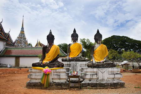 Three Buddha Brother statue beside ubosot and Chedi of Wat Phra Borommathat Chaiya Temple in Chaiya district in Surat Thani, Thailand Stock Photo