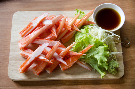 Crab sticks sashimi served with sauce and wasabi and vegetable on wooden plate in restaurant of Thailand
