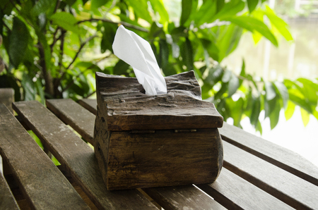 Tissue paper in wooden box on wood table in coffee shop and restaurant at Tak, Thailand