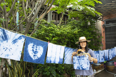 Thai women tie batik dyeing handkerchief tie batik indigo color or mauhom color and hanging process dry clothes in the sun at garden outdoor in Nonthaburi, Thailand