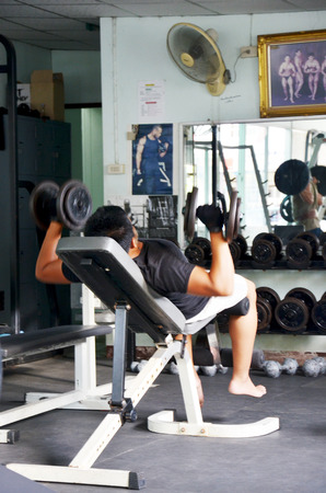 Thai man playing fitness and dumbbell in training Gym room in Nonthaburi, Thailand.