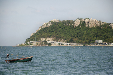 Thai man riding wooden fishing boat go to the coast of Laem thaen Scenic Lookout Bangsaen beach and sea in Chon Buri, Thailand 免版税图像 - 109941222