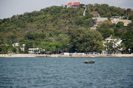 Thai man riding wooden fishing boat go to the coast of Laem thaen Scenic Lookout Bangsaen beach and sea in Chon Buri, Thailand 免版税图像 - 109942334