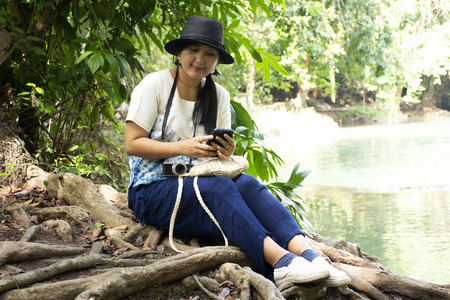 Traveler thai woman travel and posing for take photo at Chet Sao Noi small waterfalls or Namtok Chet Sao Noi National Park at Muak Lek District in the Saraburi Province of Thailand.