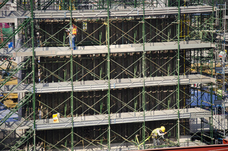 Asian people and thai workers with heavy machinery working builder new building at construction site high-rise building on scaffold at capital city in Bangkok, Thailand. Archivio Fotografico