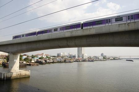 Skytrain Mass Rapid Transit Authority of Thailand MRTA or MRT Purple Line running go to bangkok across Chao phraya river at Phra Nang Klao bridge station in Bangkok, Thailand