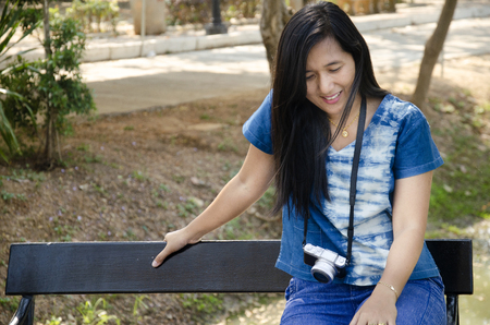 Asia thai woman travel visit and sitting on bench posing for take photo in public garden park in Sing Buri, Thailand