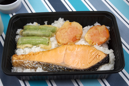 Japanese food bento box rice and fried salmon and vegetables with other cuisine on table in garden at outdoor of Japan village in Ayutthaya, Thailand 免版税图像