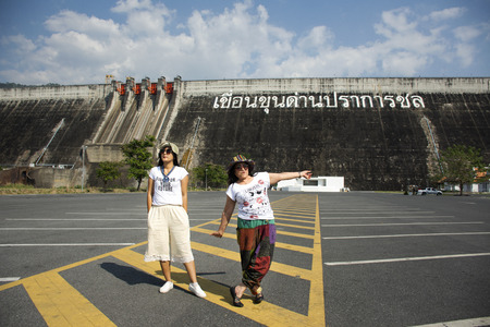 Asian thai women mother and daughter travel posing and playing on the parking front of Khun Dan Prakan Chon Dam in Nakhon Nayok, Thailand (Text thai language mean Khun Dan Prakan Chon Dam)