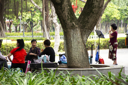 Old chinese people meet friends and sing song with playing classic musical instruments concert in Zhongshan park at Shantou or Swatow city on May 9, 2018 in Guangdong, China