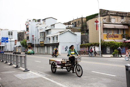 Chinese people drive and ride and bike on the road and foreigner traveler travel visit in old town area at Shantou downtown or Swatow city on May 9, 2018 in Guangdong, China
