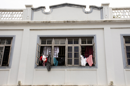 Lifestyle of chinese people hanging dry clothes in the sun at outdoor of window of classic retro vintage building at Chaozhou or Teochew on May 8, 2018 in Guangdong, China