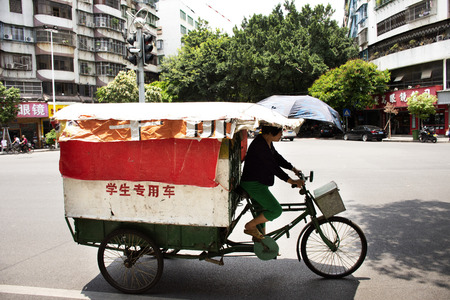Chinese old woman ride trishaw with people drive car and ride motorcycle and bike bicycle with traffic road at Chaozhou or Teochew city on May 8, 2018 in Guangdong, China