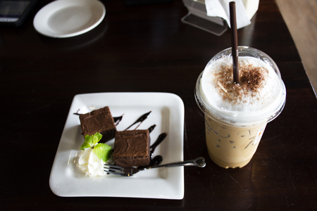 Cappuccino cold coffee with sweet dessert snack brownie cake on plate in local coffee shop for thai people and foreign travelers eating and drinks at Udonthani city in Udon Thani, Thailand