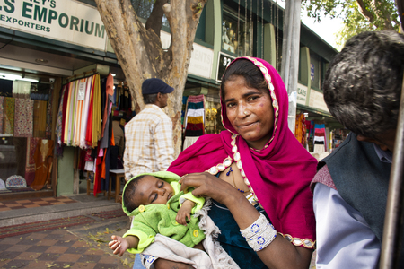 Indian women beggar or untouchables caste hold baby and begging money from travelers people at Janpath Market and Dilli Haat bazaar on March 17, 2019 in New Delhi, India
