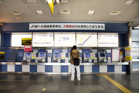 Tokyo, Japan - March 26, 2019 : Japanese people and foreign travelers passenger wait and stand in queue for buy ticket MRT train from auto vending machine at Katama Station Редакционное