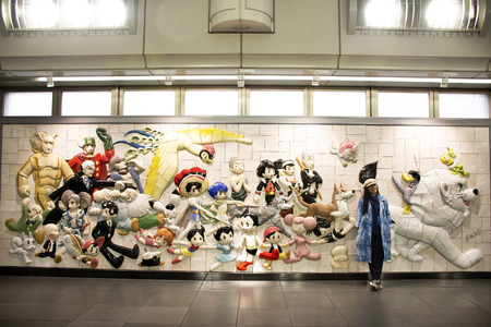 Tokyo, Japan - March 26, 2019 : Travelers thai women posing and portrait with wall art anime and hero japanese style in Ariake train JR railway Station at Koto City