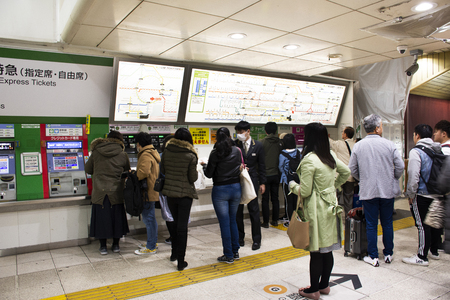 Tokyo, Japan - March 29, 2019 : Japanese people and foreign travelers passenger wait and stand in queue for buy ticket MRT trains from auto vending machine at Ginza Station