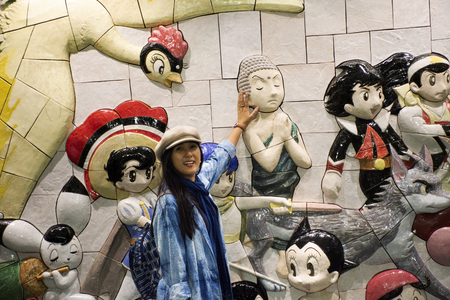 Tokyo, Japan - March 29, 2019 : Travelers thai women posing and portrait with wall art anime and hero japanese style in Ariake train JR railway Station at Koto City Редакционное